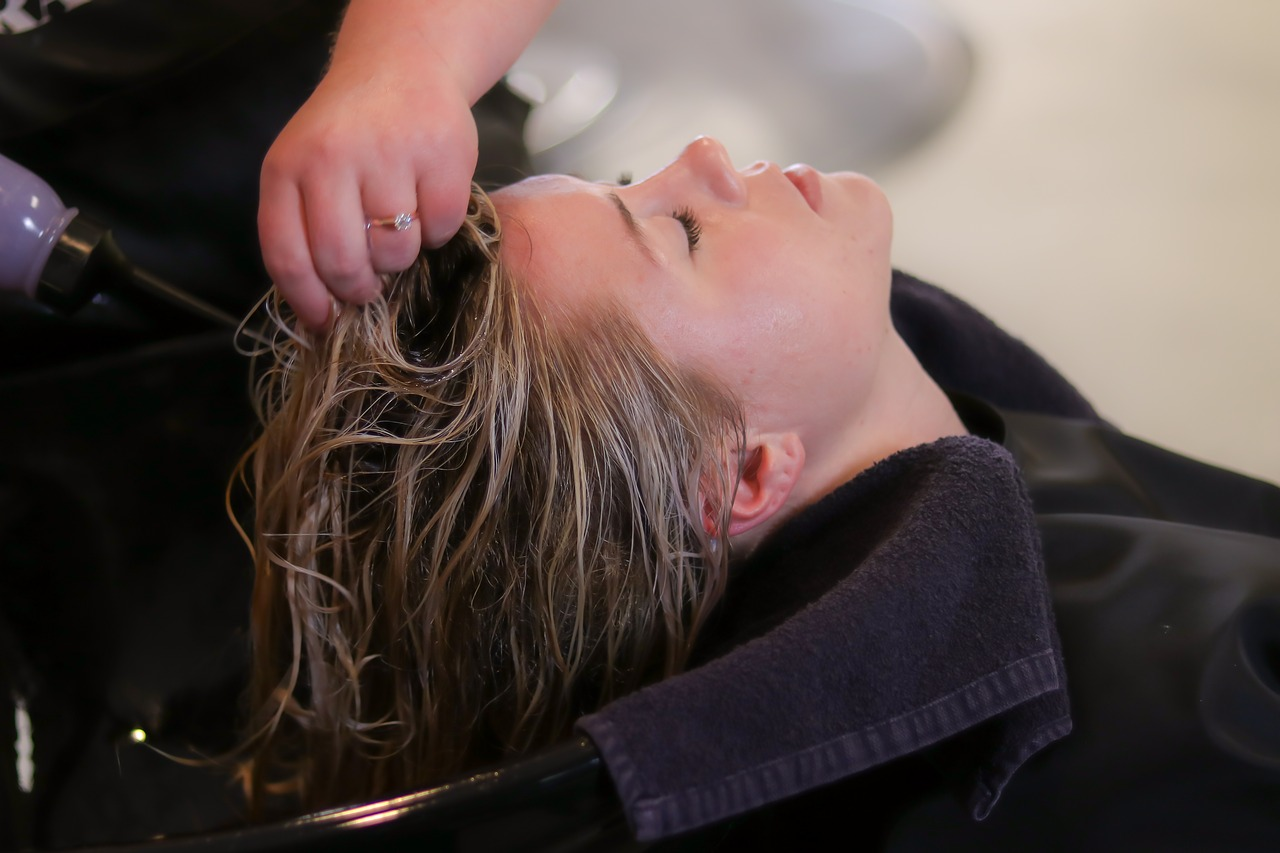 Woman having her hair washed with shampoo